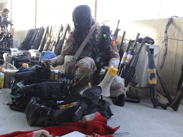 A paramilitary soldier displays weapons recovered during a raid on the Muttahida Qaumi Movement (MQM) political party's headquarters in Karachi. PHOTO: REUTERS