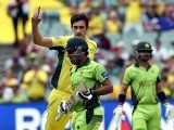 Sarfraz Ahmed walks off the field as Australia's paceman Mitchell Starc celebrates his dismissal during the 2015 Cricket World Cup quarter-final match. PHOTO: AFP