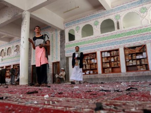 Yemeni armed men inspect the damage following a bomb explosion at the Badr mosque in southern Sanaa on March 20, 2015. PHOTO: AFP