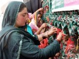 A woman ties a string on the gates of Lal Shahbaz Qalandar's shrine in Sehwan during the 763rd Urs. PHOTO: INP