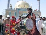 A man beats a drum during a dhamaal outside the shrine of Lal Shahbaz Qalandar in Sehwan during the 763rd Urs. PHOTO: APP