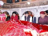 Advisor to Sindh Chief Minister Dr Abdul Qayyum laying a ceremonial blanket on Lal Shahbaz Qalandar's grave during 763rd Urs celebrations. PHOTO: APP