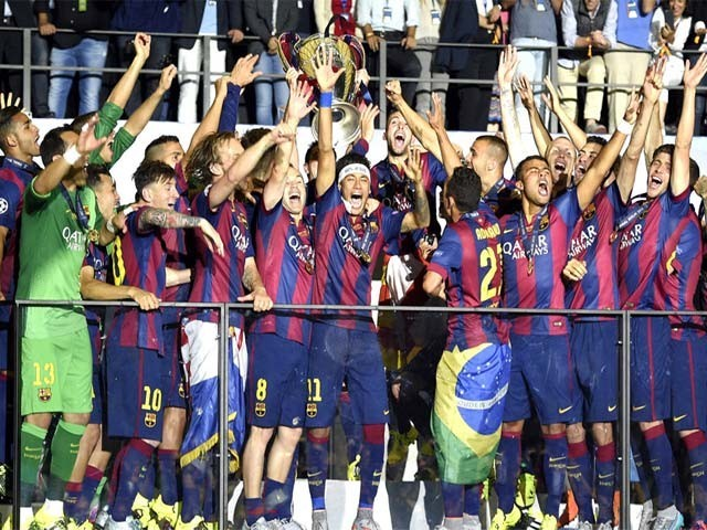 Barcelona's players celebrate with the trophy after the UEFA Champions League Final football match between Juventus and FC Barcelona at the Olympic Stadium in Berlin on June 6, 2015.  FC Barcelona won the match 1-3. PHOTO: AFP