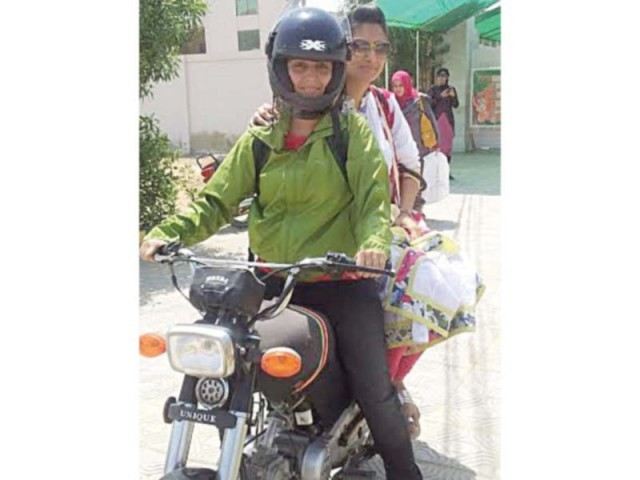 Wearing a helmet, 26-year-old Tayyaba poses on her motorcycle while her friend sits behind her. She is one of the few women who ride a motorcycle against the norm in Karachi. PHOTO: EXPRESS