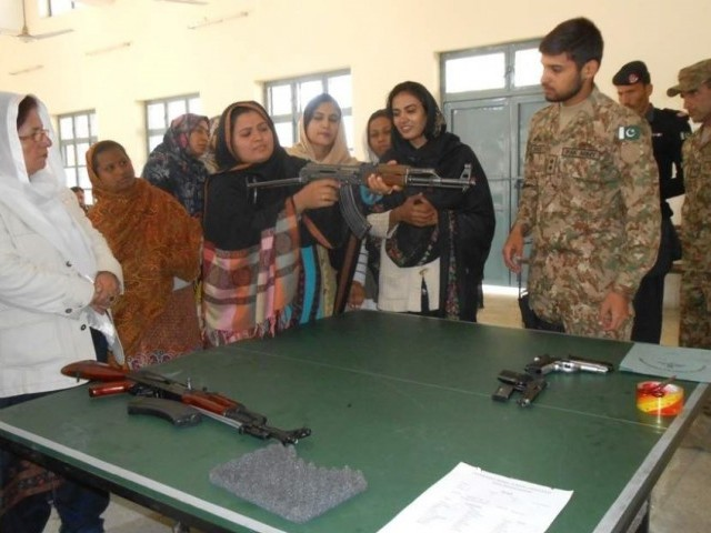 An army lieutenant showing a teacher how to handle firearms. PHOTO: Hairan Momand / Express Tribune