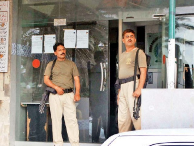 Security guards stand outside the office of the Sindh Building Control Authority at Civic Centre after the Rangers raided the office. The CM has reminded the Rangers that they are transgressing their authority. PHOTO: FILE