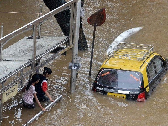 Indian pedestrians wade through a waterlogged neighbourhood in Mumbai on June 19, 2015. Heavy monsoon showers lashed India's financial capital resulting in waterlogging in low lying areas of the city disrupting normal life. PHOTO: AFP