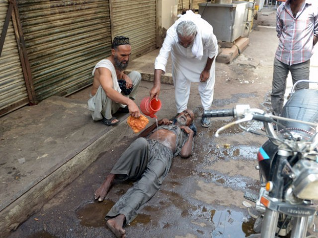 A resident helps a heatstroke victim at a market area during a heatwave in Karachi on June 23, 2015. PHOTO: AFP