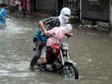 A man pushing his motorcycle in the rain in Rawalpindi.PHOTO: INP