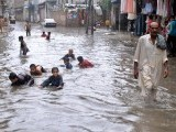 Children playing in standing water in Rawalpindi after the monsoon rain on Tuesday. PHOTO: INP