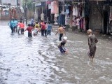 Children playing in standing water in Rawalpindi after the monsoon rain on Tuesday. PHOTO: NNI