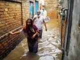 People walking in the flooded streets of Rawalpindi after the monsoon rain on Tuesday. PHOTO: ONLINE