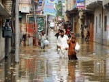 People walk in standing rain water in Rawalpindi. PHOTO: ONLINE