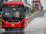 A metro bus seen splashing water gathered on its track in Islamabad on Tuesday. PHOTO: ONLINE