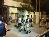 Rangers take MQM leader into custody following a raid on Khursheed Begum Memorial Hall.