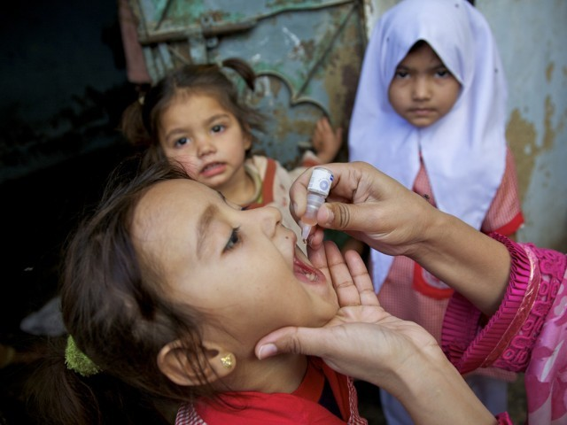 Health worker vaccinating a child against polio outside her home during Polio National Immunization Day (NID), while her sisters watching in Sherpow in Landhi town, Karachi Pakistan. PHOTO: CDC