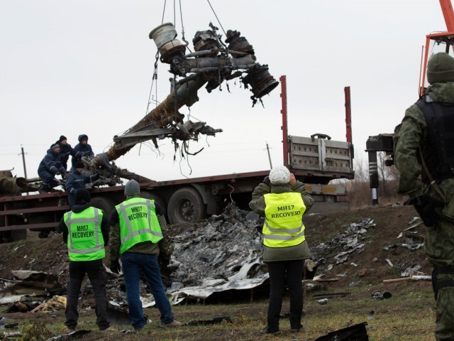 Members of the Dutch export team watch as parts of the wreckage of the Malaysia Airlines Flight MH17 are removed and loaded on a truck at the crash site near the village of Grabove in eastern Ukraine, on November 16 2014. PHOTO: AFP