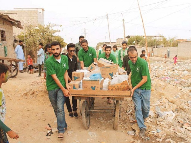 Volunteers from the Robin Hood Army in Pakistan distributing food to the residents of Bilal Colony in Karachi. PHOTO CREDIT: ABBAS MAHMUD
