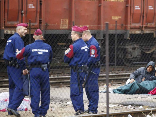 Hungarian police officers stand next to migrants at the Bicske railway station in Bicske, Hungary, September 4, 2015. PHOTO: REUTERS