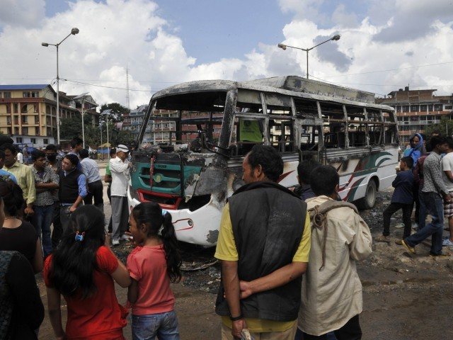 Nepalese bystanders gather around the charred remains of a bus, which was set alight during a general strike call by the hardline breakaway faction of former Maoist rebels (Communist Party of Nepal-Maoist), in Kathmandu on September 20,2015. PHOTO: AFP