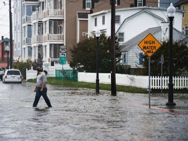A man crosses a flooded street in Ocean City, Maryland, on October 3, 2015 as coastal flooding warnings are issued along the US east coast as heavy rains, partly fueled by Hurricane Joaquin, continue to fall on the area. PHOTO: AFP