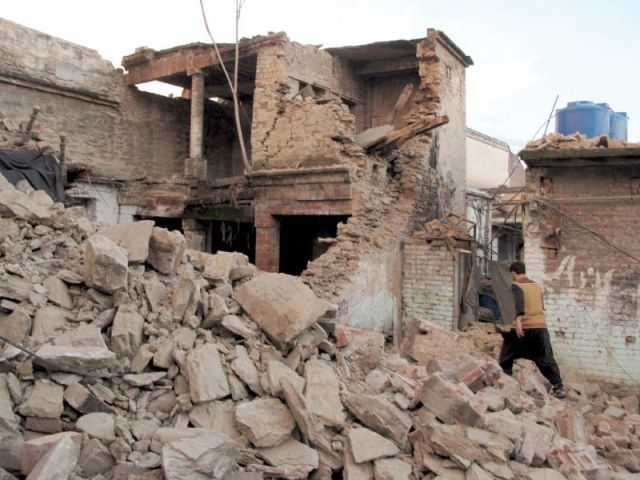 A man walks past the rubble of a house in Mingora, Swat. PHOTO: REUTERS
