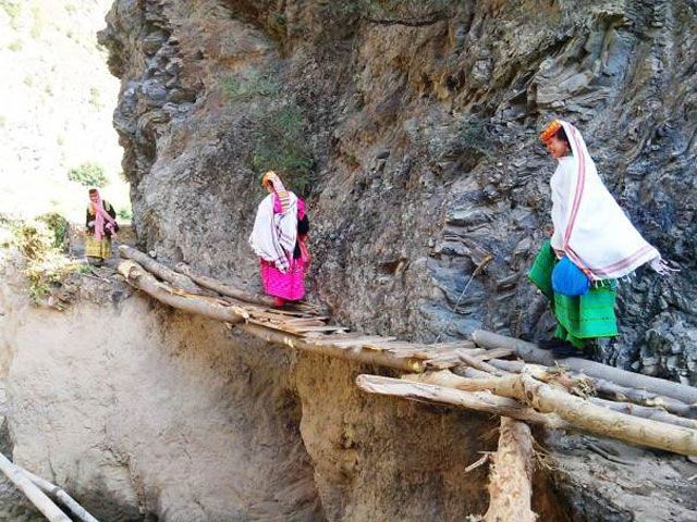 Kalash women in Hindu Kush mountains walk along a makeshift bridge after paths were swept away by torrential rainfall. PHOTO: REUTERS