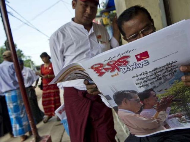 Myanmar men read a newspaper showing a picture of opposition leader Aung San Suu Kyi, seen at right with Tin Oo, the National League for Democracy (NLD) party chairman, outside the NLD headquarters in Yangon on November 11, 2015. PHOTO: AFP