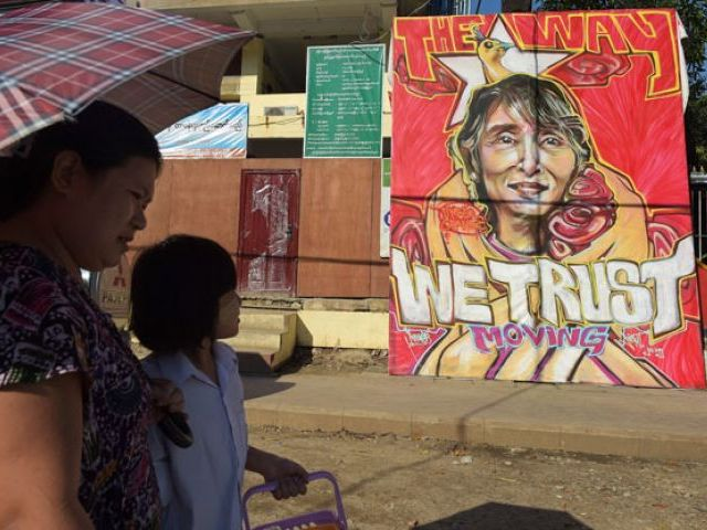 People walk past a graffiti depiction of Myanmar's opposition leader Aung San Suu Kyi outside the headquarters of the National League for Democracy party (NLD) in Yangon on November 13, 2015. PHOTO: AFP