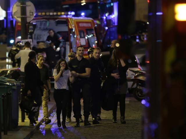 People are evacuated following an attack at the Bataclan concert venue in Paris, on November 13, 2015. At least 18 people were killed in multiple attacks in Paris Friday, including one near the Stade de France sports stadium. PHOTO: AFP