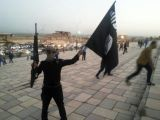 a-fighter-of-the-isil-holds-a-flag-and-a-weapon-on-a-street-in-mosul-3-2-3-2-2