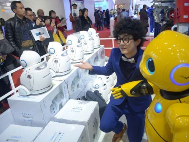 This picture taken on November 24, 2015 shows a visitor posing for a photo with a robot during the World Robot Conference in Beijing.  Beijing wants to be the first to welcome the new mechanical overlords and the World Robot Conference showcases a vision of automatons with Chinese characteristics.           PHOTO: AFP