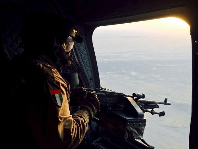 A soldier from the United Arab Emirates armed with a machine gun watches over Yemeni territory while riding a Chinook helicopter en route to a Saudi-led coalition air base in the kingdom September 17, 2015. PHOTO: REUTERS