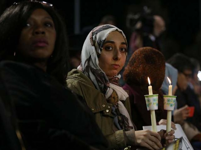 SAN BERNARDINO, CA - DECEMBER 03: People hold candles as they attend a vigil at the San Manuel Stadium to remember those injured and killed during the shooting at the Inland Regional Center were killed on December 3, 2015 in San Bernardino, California. Police continue to investigate a mass shooting at the Inland Regional Center in San Bernardino that left at least 14 people dead and another 17 injured on December 2nd. PHOTO: AFP