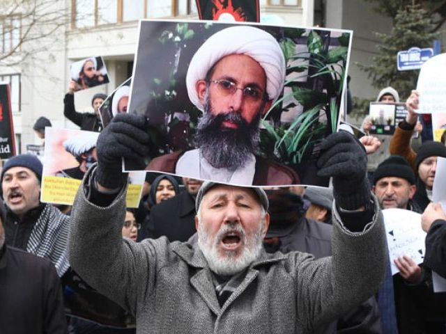 Iranian and Turkish demonstrators hold pictures of Shia cleric Sheikh Nimr al-Nimr as they protest outside the Saudi Embassy in Ankara, on January 3, 2016, to protest against the execution by Saudi Arabia of a prominent Shia cleric which they saw as a deliberate sectarian aggression. PHOTO: AFP