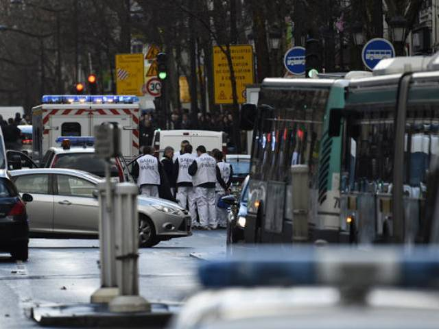 Rescue workers are seen at the Boulevard de Barbes in the north of Paris on January 7, 2016, after police shot a man dead as he was trying to enter a police station in the Rue de la Goutte d'Or. PHOTO: AFP