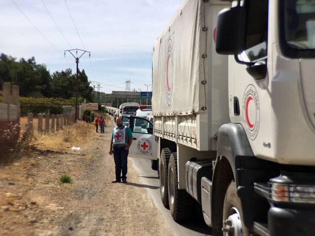 A file handout picture released by the International Committee of the Red Cross (ICRC) shows a relief convoy carrying medical items having a stopover 10 km from Syrian cities of Zabadani and Madaya, some 50 km northwest of Damascus, on October 18, 2015. PHOTO: AFP