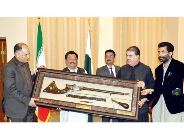 Balochistan CM Sanaullah Zeghri presents an antique gun to the Iranian province of Sistan-Baluchestan Governor Ali Osat Hashemi. PHOTO: BANARAS KHAN/EXPRESS
