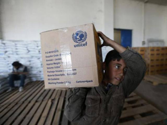 A boy receives humanitarian aid in Duma, Damascus March 29, 2014. PHOTO: REUTERS