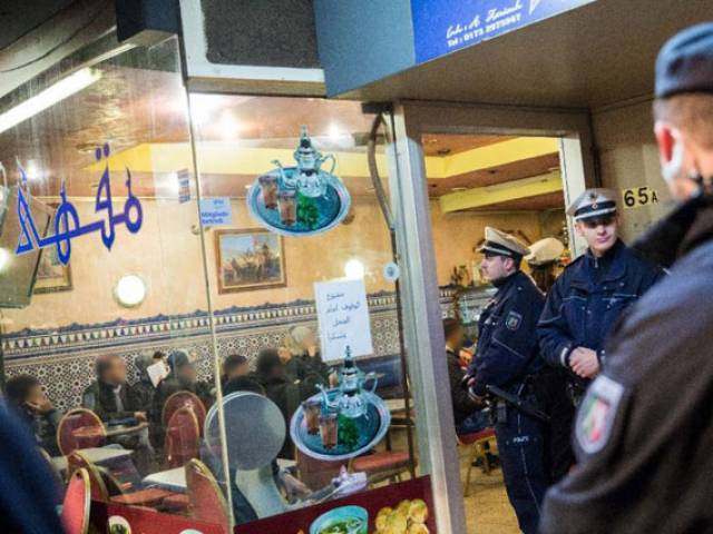 Policemen stand in front of a cafe in the so-called Maghreb-district of Duesseldorf, western Germany, during a raid on January 16, 2016. PHOTO: AFP