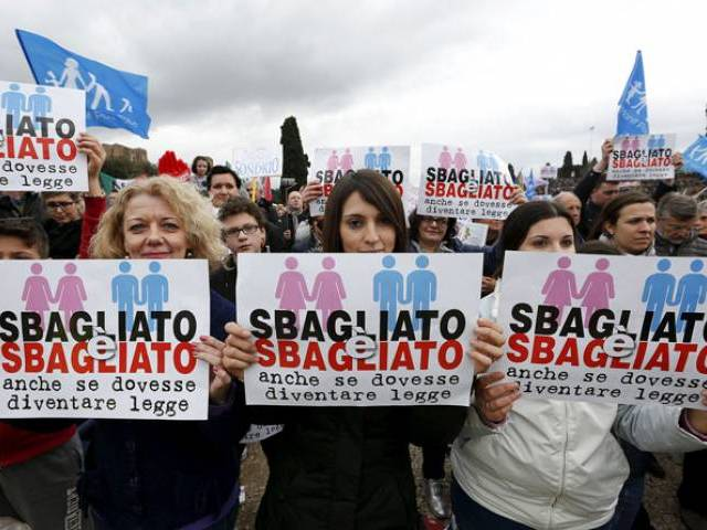 "Protesters hold signs reading ""It is wrong even if it becomes law"" during a rally against same-sex unions and gay adoption in Rome, Italy January 30, 2016. PHOTO: REUTERS"