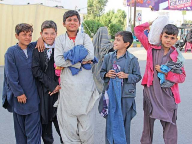 Street children were happy to grab an assortment of clothes from Wall of Kindness at Sea View on Saturday. The adults preferred to take home bags of ration. PHOTO: AYSHA SALEEM/EXPRESS