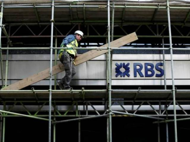 A scaffolder carries a plank past a sign for RBS on a building undergoing renovation in London March 21, 2014. PHOTO: REUTERS