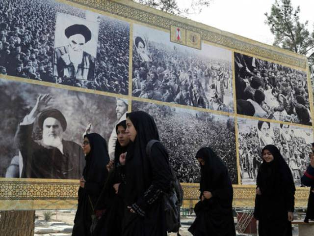 Iranian schoolgirls walk past a giant board displaying pictures of the late founder of the Islamic Revolution Ayatollah Ruhollah Khomeini, as Iranians mark the start of 10 days of celebrations for the 37th anniversary of the Islamic revolution on February 1, 2016 at the Behesht-e Zahra (Zahra's Paradise) cemetery in southern Tehran. PHOTO: AFP