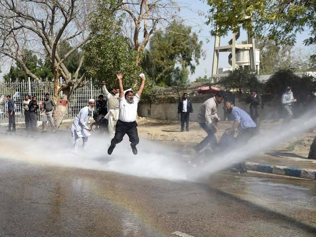 PIA employees shout slogans as police use a water cannon on them during a protest near the Karachi airport. PHOTO: AFP