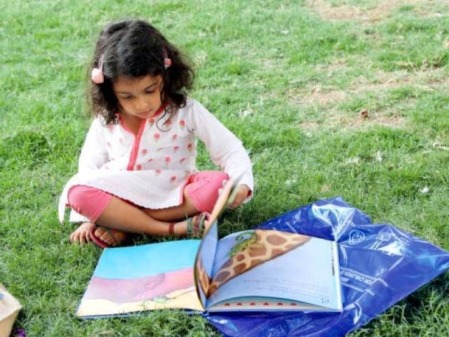 A little girl flips through her book in the Beach Luxury lawn at the literature festival on Friday.
