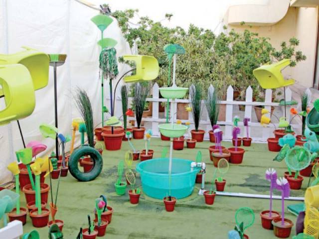 An art installation shows a garden made of plastic utensils, toilet brushes and discarded shoes.