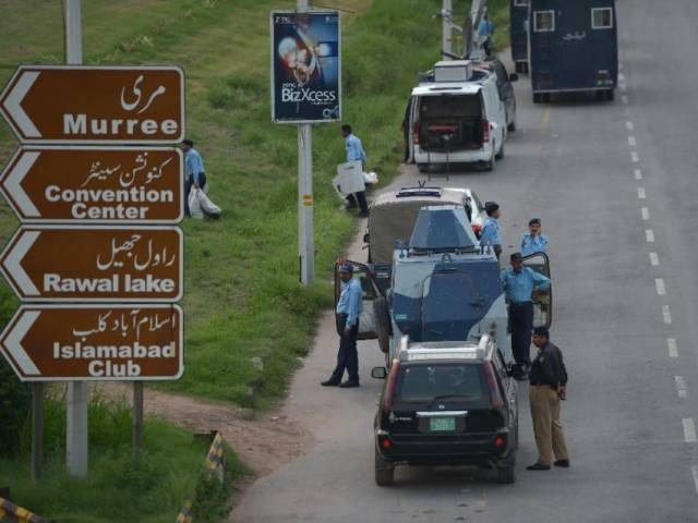 Pakistani policemen stand next to their vehicles in Islamabad on August 9, 2014. PHOTO: AFP