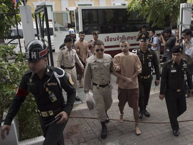 Foreign suspects in the August 17 Erawan shrine bombing identified by the ruling junta as Adem Karadag (C) and Yusufu Mieraili (C, back L) arrive at a military court in Bangkok on February 16, 2016.  The two Uighurs, accused over last year's deadly bombing, are set to enter a plea at a military court. PHOTO: AFP