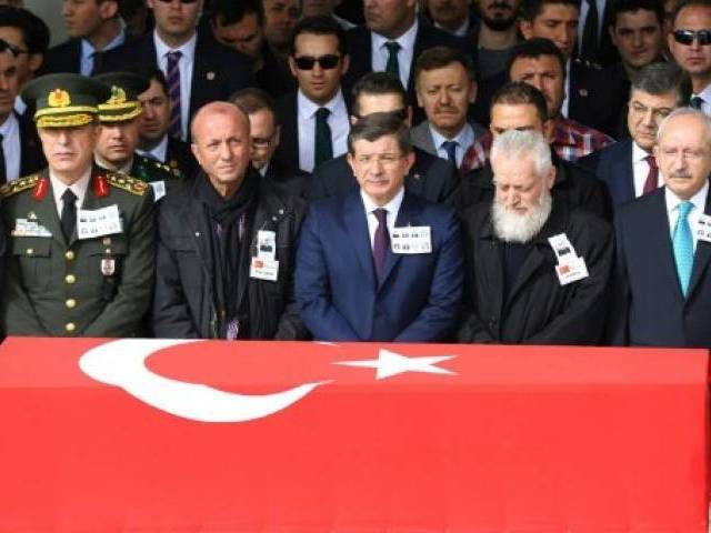 Turkish Prime Minister Ahmet Davutoglu (C) stands behind the flag-draped coffin of a car bombing victims during a funeral ceremony at Kocatepe Mosque in Ankara on February 19, 2016. PHOTO: AFP